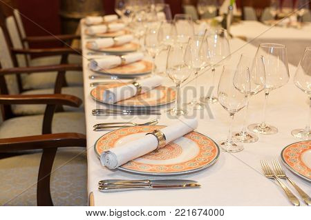 feast, treatment, wedding concept. long table covered with white cloth and served for reception guests, there are shining glasses for alcohol and decorated tableware in classic style