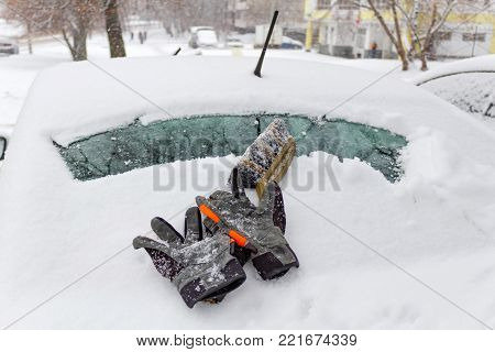 Protective gloves and brush on the snow cowered car rear window