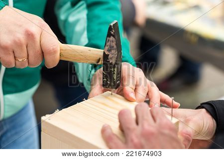 creativity, saving environment, producing concept. close up of male arms, he is making wooden house for birds and with help of hammer and nails he is bonding few unpainted boards in one box