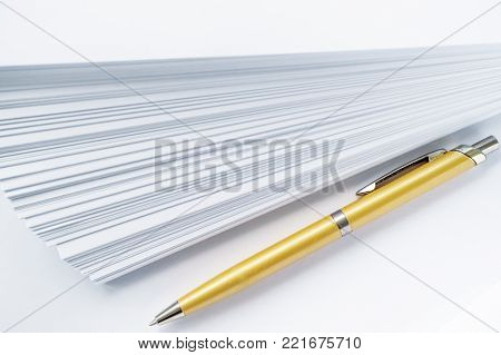 gold ball point pen lying on the pile of paper for those who write, white background