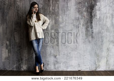 A Young Woman In A Beige Cardigan, Jeans And Black Heels