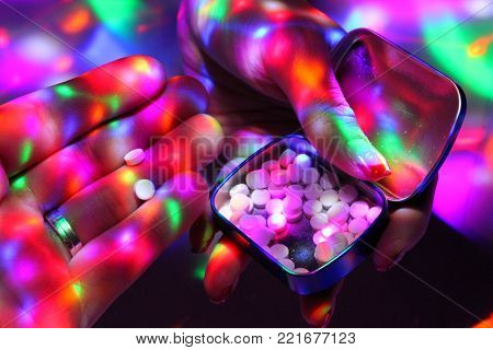 A man takes ecstasy from the box the dealer holds./Womans hand with nice nails offers ecstasy on a disco.