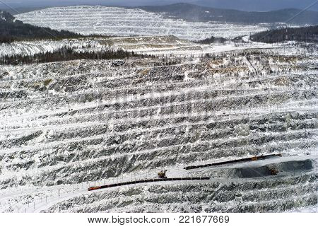 view from above on a snow-laden working quarry for the extraction of bauxite ore with excavators and freight trains
