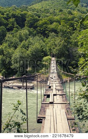 The hanging bridge over mountain river photo