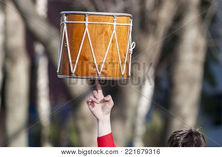 The musician rotates Dhol on one finger. Dhol can refer to any one of a number of similar types of double-headed drum widely used, with regional variations, throughout the Indian subcontinent.