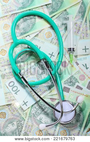 medical treatment and high cost for a good health care service concept: green stethoscope on money polish zloty paper banknotes