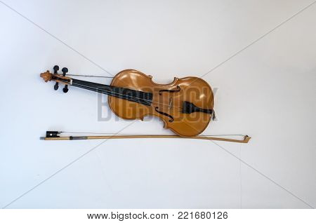 Classical cello on white wall background. Vintage musical instrument.