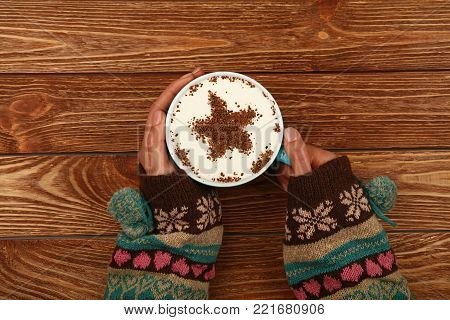 Close up two woman hands hold and hug big full cup of latte cappuccino coffee with star shaped chocolate on milk froth over brown wooden table, elevated top view, directly above