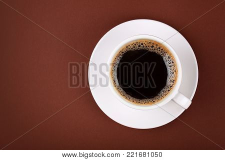 Close up white cup full of black instant coffee with froth on porcelain saucer over brown paper background, close up, elevated top view, directly above