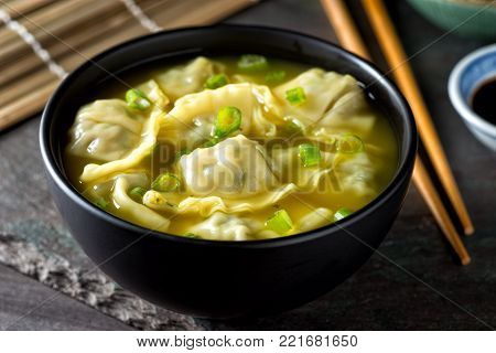 A bowl of delicious chinese wonton soup with green onion garnish.