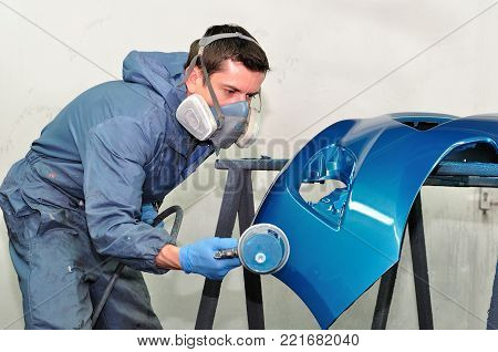 Proffesional car body repair, Painting blue bumper.