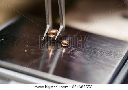 The work of jewelers. The jeweler weighs the copper granules on a digital scale. Selective focus. Macro photo.