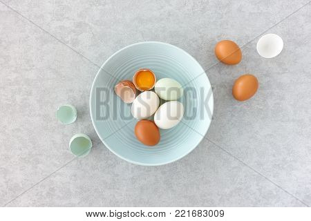 Blue eggs, brown eggs and duck eggs, whole and halves, in a pastel blue bowl on grey textured background. Top view.