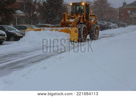 January 04 2018 NY New York: Snow-removing machine cleans the street of the city park from the snow in the morning snow-covered trees. Cleaning road from snow storm.