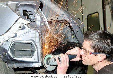 Body worker grinding welds car body at repair.