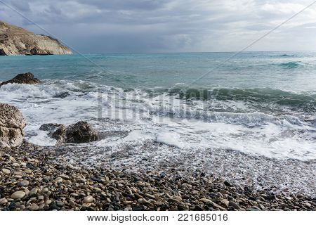 Picture of frothy sea, pebble, cloudy sky during day