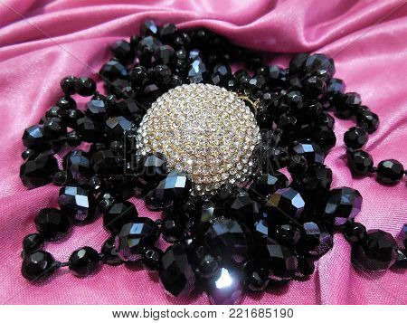 a golden pendant strewn with small shimmering pebbles surrounded by black faceted glass beads on the lilac satin fabric laid in waves