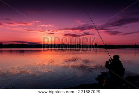 fantastic landscape, multicolor sky over the lake. majestic sunrise. Fishing feeder at sunset. Fisherman silhouette at sunset. use as background. series with many color variations. creative images.