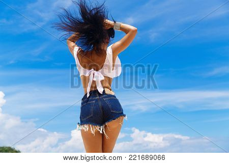 Young Beautiful Brunette With Hair Flying In The Wind Having Fun On A Tropical Beach With Her Back T
