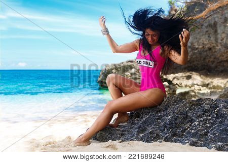 Young beautiful brunette with hair flying in the wind having fun on a tropical beach. Summer vacation concept.