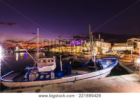Fishing boat docked at the Limassol old port in Cyprus, next to the Marina. A view of the harbor, the mediterranean sea, the water, boat fish nets, equipment, restaurants and shops at sunset to dusk.