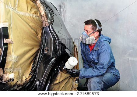 Worker painting a  black car in a paint boath.