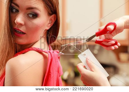 Woman girl removing cutting label board price tag off new dress cloth with scissors. Female after shopping.
