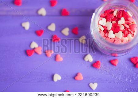 Open Glass Jar Filled With Many Little Candies In Form Of Hearts On Purple Bokeh Background