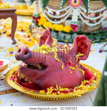 Red pig head on plate and flower around of head for ceremony or sacrifice