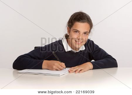 Schoolgirl writing at her desk with a happy expression