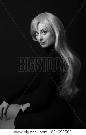 Photo shooting indoors. On a black background. A woman with long white hair, wearing a black jacket.