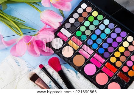 Cosmetic Brushes With Eyeshadow Palette On Tender White Lace And Bouquet Of Tulips On Blue Wooden Ba