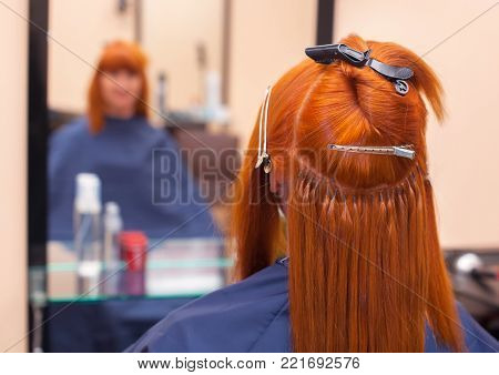 The hairdresser does hair extensions to a young, red-haired girl, in a beauty salon. Professional hair care.