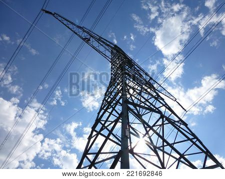 Photo of a large transmission tower under the blue sunny sky