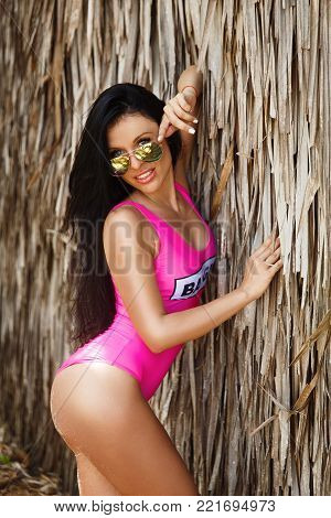 Young Beautiful Brunette Girl In Front Of The Huts Made Of Palm Leaves On The Beach Of A Tropical Is