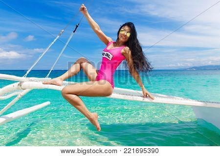 Young Beautiful Brunette Having Fun On A Tropical Beach On The Sailboat. Summer Vacation Concept.