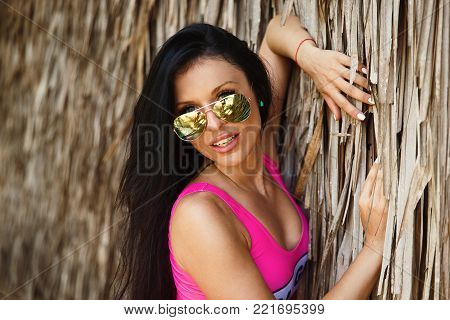 Close-up Portrait Young Beautiful Brunette Girl In Front Of The Huts Made Of Palm Leaves On The Beac