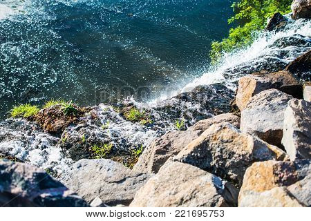 Waterfall in Shevchenko park on Dnepr river in Ukraine. Nature, Water, Stones, Sunny Day, Dnipro city.