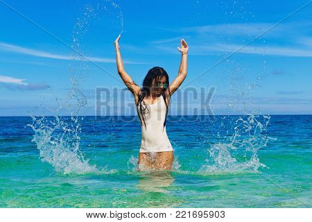 Beautiful brunette in a wet t-shirt resting on a tropical sea. The concept of summer vacation.