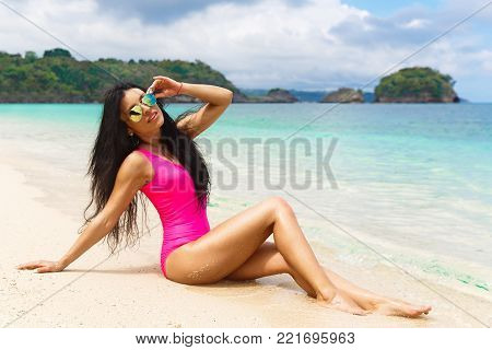 Beautiful brunette on the shore of a tropical beach. Summer vacation concept.