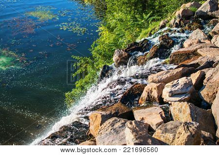 Waterfall in Shevchenko park on Dnepr river in Ukraine. Nature, Water, Stones, Sunny Day, Dnipro city. Picturesque Background
