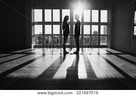 A young boy and girl with long blond hair standing in front of the window. Black and white art monochrome photography. Black and white creative photography. Black and white conceptual image. Beautiful black and white background. Black and white portrait.
