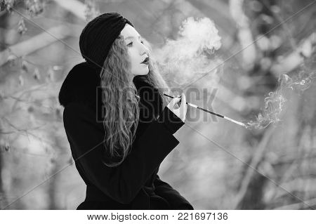 Black and white art monochrome photography. Black and white creative photography. Black and white conceptual image. Beautiful black and white background. Black and white portrait. A woman in a black coat on background of a winter forest