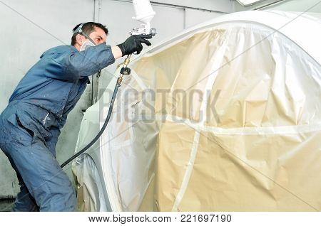 Professional body shop worker painting white car.