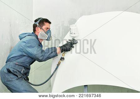 Professional body shop worker painting white car bonnet.