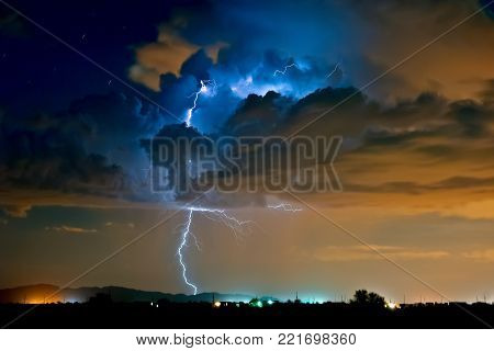 A lightning storm moving over the Metro-Phoenix area of Arizona during the 2015 Monsoon season. The blue hues of the lightning is from the white balance setting. The orange glow in the clouds is from the street lights of Phoenix shining up into the bottom