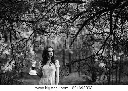 Very cute young girl with a kerosene lamp. Black and white art monochrome photography. Black and white creative photography. Black and white conceptual image. Beautiful black and white background. Black and white portrait.