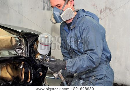 Professional body shop worker painting black car.