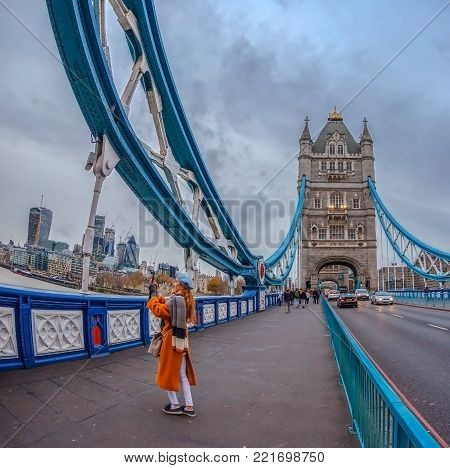 LONDON, ENGLAND - NOVEMBER 27, 2017: Wide angle view architecture from Tower Bridge with tourists and London over river Thames with skyscrapers.
