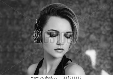 Lovely girl with tanned skin and white hair listening to music. Black and white art monochrome photography. Black and white creative photography. Black and white conceptual image. Beautiful black and white background. Black and white portrait.